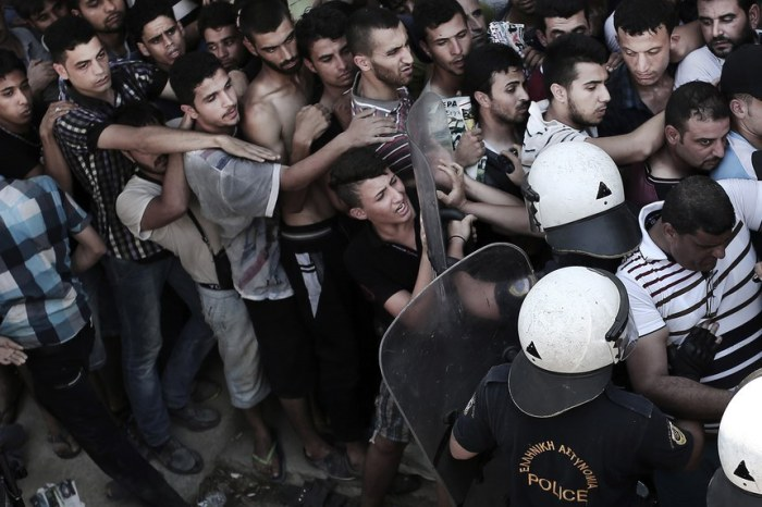 A policeman (2nd-R) pushes a migrant as hundreds wait to complete a registration procedure by the police at a stadium on the Greek island of Kos on August 12, 2015. Tensions on the tourist island are high with its mayor claiming there were 7,000 migrants stranded on Kos, which has a population of only 30,000 people. A Kos police officer was suspended on August 10 after being filmed slapping and shoving migrants queueing outside the local police station as they waited to be documented so they could go on to Athens. The UN refugee agency's division for Europe said 124,000 refugees and migrants have landed in Greece since the beginning of the year. AFP PHOTO / ANGELOS TZORTZINIS (Photo credit should read ANGELOS TZORTZINIS/AFP/Getty Images)